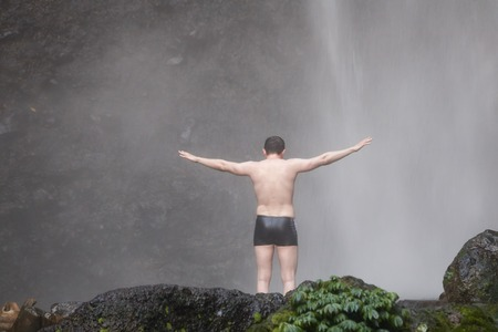A man standing uder Sekumpul waterfall in Bali. View from back.