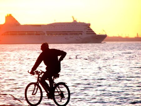 male cycling and yellow sunset and ship at background