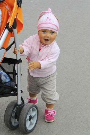 baby daughter learning walking with here troller Stock Photo