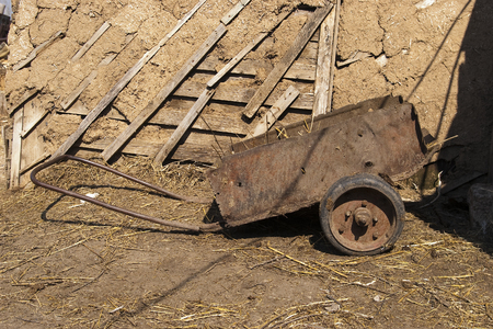 Cart for removal manure near wooden shed