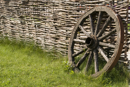 Old wooden wheel in the grass near the fence