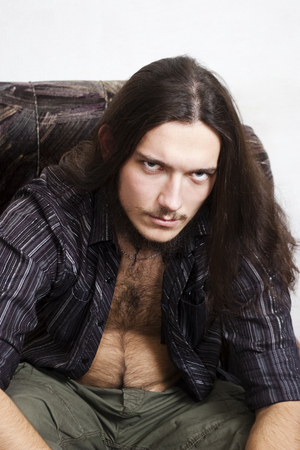 Bearded long-haired young man in an unbuttoned shirt, sitting in a chair