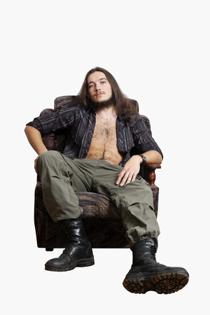 Bearded long-haired young man in an unbuttoned shirt and ankle boots, sitting in a chair