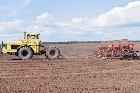 Tractor with seeder in the field Stock Photo
