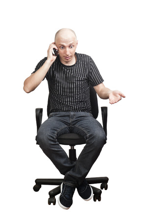 Man sitting in an office chair, talking on mobile phone