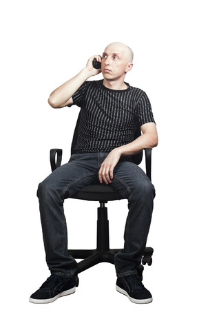 Man talking on a cell phone while sitting in an office chair