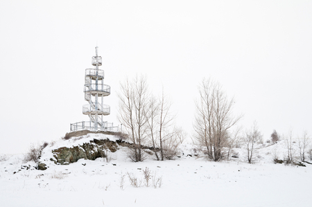 Lighthouse on the shore of the frozen lake Stock Photo