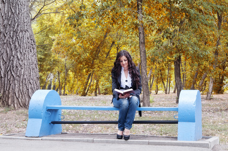 Girl with the book on a bench in autumn park. Stock Photo