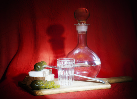 Still life with vodka in a decanter and snack