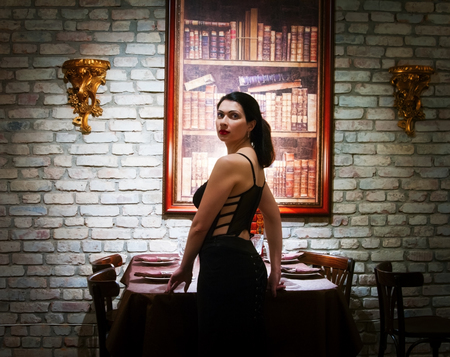 Woman in a corset, standing near the restaurant table