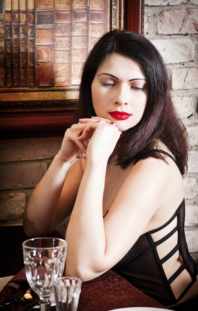 Beautiful brunette in a corset for a restaurant table Stock Photo
