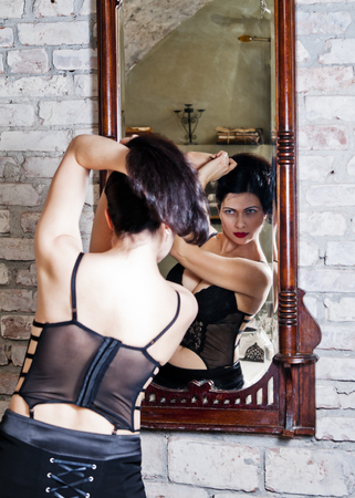 coif: Woman in a corset in front of a mirror