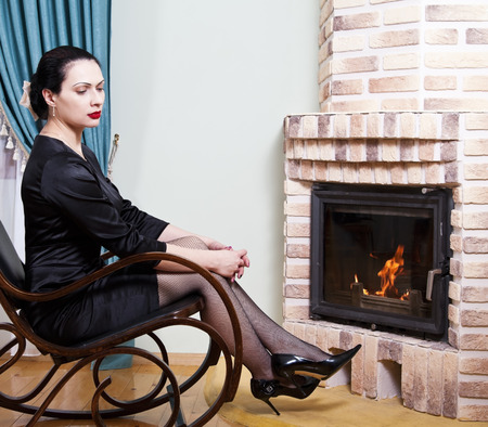 Woman sitting in a rocking chair in front of a fireplace