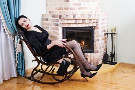 Femme fatiguée dans une chaise à bascule devant une cheminée Banque d'images - 76336943
