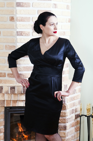 Woman in a black evening dress posing in the interior with a fireplace Stock Photo