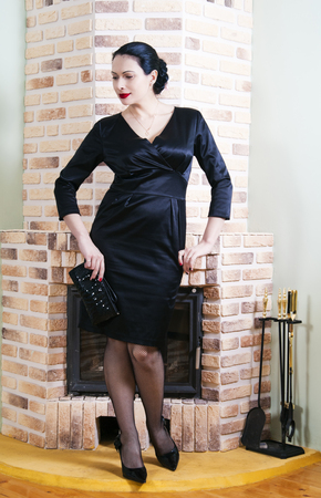 Woman in evening dress posing in the interior with a fireplace Stock Photo