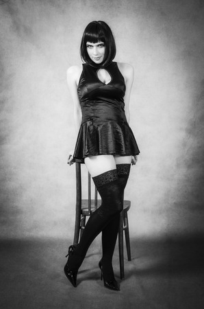 Girl in black stockings, standing leaning on the back of a chair