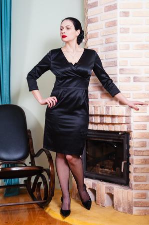 Woman in a black evening dress standing near fireplace Stock Photo