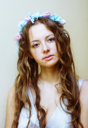Portrait of beautiful girl with flowing hair and a flower wreath on head