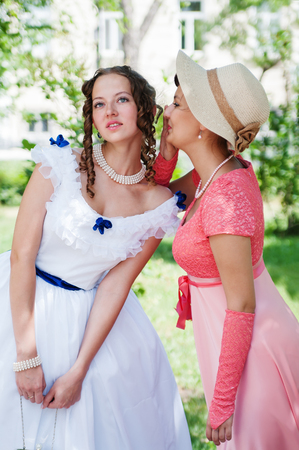 Two girls in vintage dresses share secrets Editorial