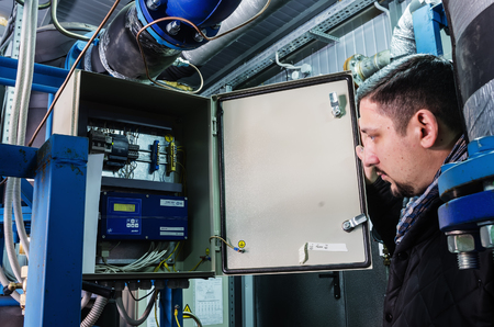 heat register: Specialist examines the device for recording heat at a heat-regulating substation