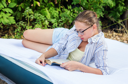 Girl with glasses reading a book, lying on an air mattress in the woods