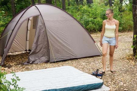 Tourist camp. She pumps up an inflatable mattress