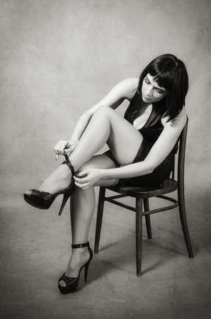 plunging: Brunette sitting on the chair putting on shoes