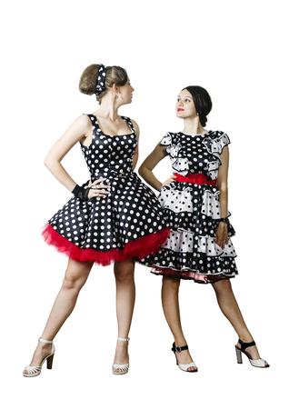 sitter: Two girls dressed in the style of pin-up on a white background looking at each other