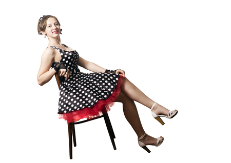 Girl pin-up style, sitting on a chair. White background, isolated