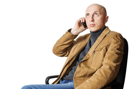 Man in the yellow jacket is calling on mobile phone while sitting in an office chair Stock Photo