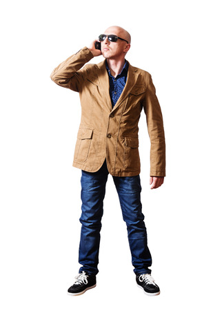 Man in a jacket and jeans talking on cell phone