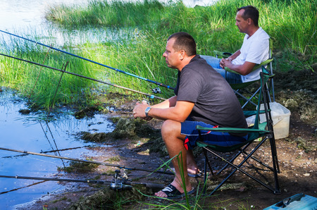 Fishermen fish for fish on the shore. Photo taken at the Ural River oxbow lake near the city of Orenburg, Russia. 08.27.2016 Editorial