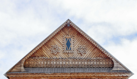 The carved pediment of a wooden house against the sky