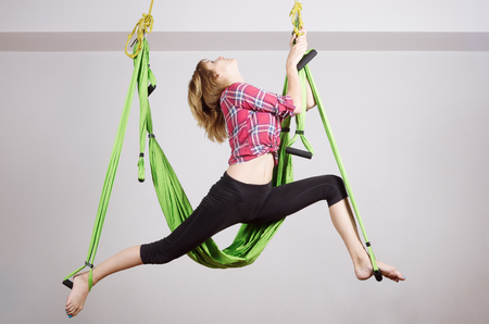 Girl performs exercises with a hammock for yoga  Photo taken in Russia, in the city of Orenburg in the fitness club