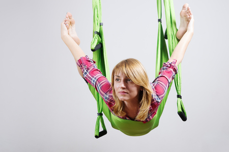 The girl performs exercises in a hammock for yoga  Photo taken in Russia, in the city of Orenburg, in the fitness club