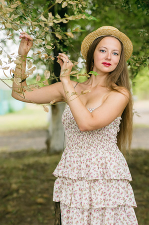 Girl in a straw hat and summer dress posing in a city park  Photographed in Russia, Orenburg
