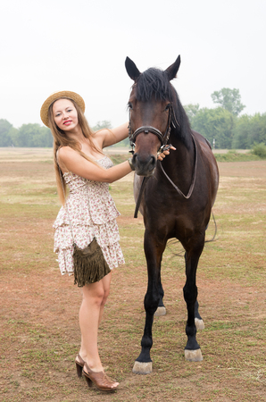 Beautiful blonde in a straw hat and summer dress, photographed with a horse  Photo taken in Russia, at the hippodrome of the city of Orenburg Stock Photo