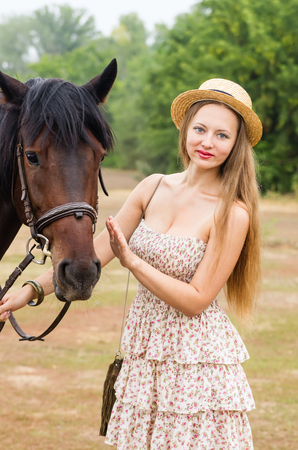 Beautiful girl in a straw hat and summer dress posing with a horse  Photo taken in Russia, at the hippodrome of the city of Orenburg