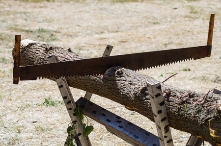 Two-handed saw in a beam on a trestle  Photo taken in Russia, in the courtyard of a rural house Фото со стока