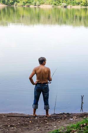 Man catches fish on a fishing pole, on the shore of a lake  The picture is taken on an old man of the Ural River, near the city of Orenburg. 9032017