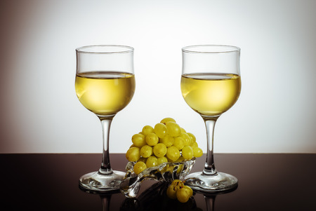 Two glasses of wine and a bunch of grapes on a glass plate  Photo taken in a personal photographer studio