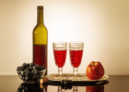 Still life with red wine  A bottle of red wine, two glasses, an apple, and a cup with grapes standing on a table