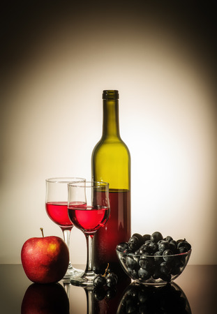 Still life with red wine  Open bottle of red wine, two glasses, an apple, and a cup with grapes standing on a table