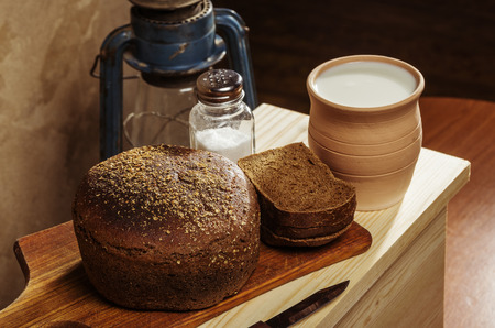Rye bread with salt on a cutting board, ceramic pot with milk. Still-life in the rustic style Stock Photo