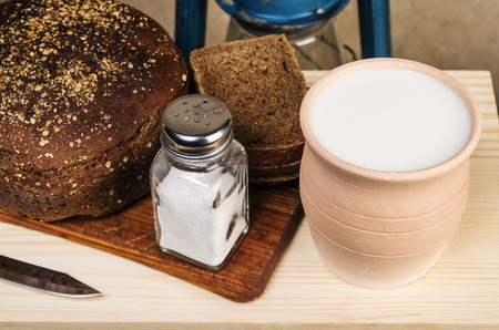 Milk in a clay pot, bread, salt on a cutting board. Still-life in the rustic style