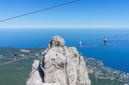 Suspension bridge over the abyss. Russia, Republic of Crimea. 06.13.2018. Suspension bridge on Mount Ai-Petri. Extreme attraction for tourists Фото со стока - 113921398
