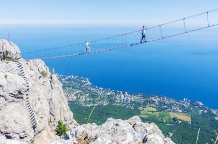 Suspension bridge over the abyss. Russia, Republic of Crimea. 06.13.2018. Suspension bridge on Mount Ai-Petri. Extreme attraction for tourists Фото со стока - 113921401