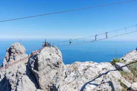 Suspension bridge over the abyss. Russia, Republic of Crimea. 06.13.2018. Suspension bridge on Mount Ai-Petri. Extreme attraction for tourists Фото со стока - 113921403