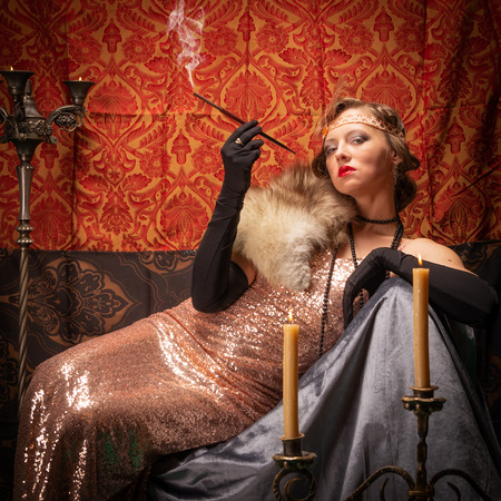Girl in an evening dress with a cigarette. Studio retro style photo